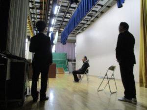 舞台袖には、佐藤校長と共に、生徒の誘導や表彰状の手配を淡々と進める水本先生(中学54期生)。