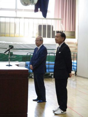 表彰のため壇上に立つ佐藤正光学校長と鈴木晋副会長