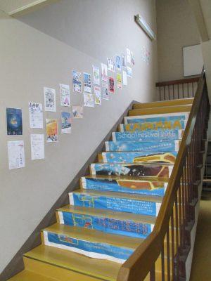もう少し進むと、カラフルなScF掲示が・・・生徒玄関と事務室の間の階段です。その手摺は中学校舎当時のまま健在です。